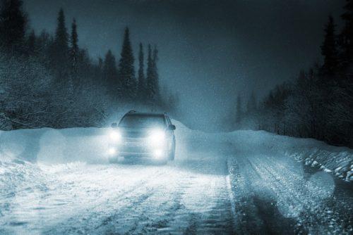mobil yang melaju di malam hari dengan lampu yang terang