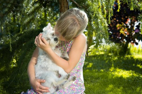 Little Girl Cuddling Her Puppy Close