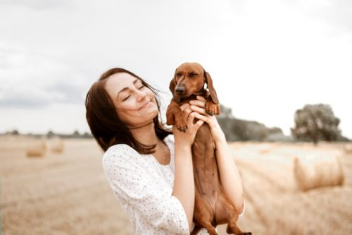 wanita menggendong anjingnya